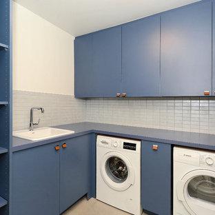 Bild på en mellanstor funkis blå u-formad blått tvättstuga enbart för tvätt, med en nedsänkt diskho, släta luckor, blå skåp, laminatbänkskiva, vita väggar, betonggolv, en tvättmaskin och torktumlare bredvid varandra och beiget golv