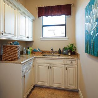 Esempio di una lavanderia tropicale con lavello sottopiano, ante con bugna sagomata, ante beige, top in granito, pareti beige, pavimento in pietra calcarea e pavimento beige