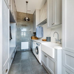 Photo of an expansive country galley utility room in Melbourne with a farmhouse sink, shaker cabinets, grey cabinets, quartz benchtops, concrete floors, grey floor, white benchtop, grey walls and a side-by-side washer and dryer.