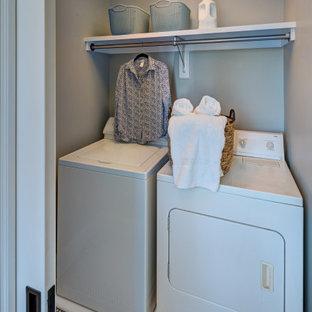 Klassisk inredning av en liten linjär liten tvättstuga, med blå väggar, klinkergolv i keramik och en tvättmaskin och torktumlare bredvid varandra