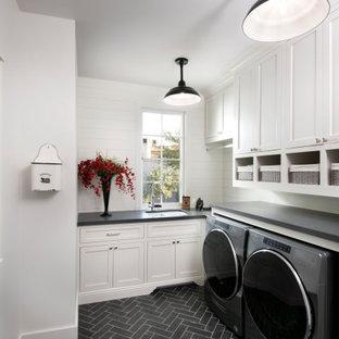 Inredning av en klassisk svarta svart tvättstuga, med en dubbel diskho, skåp i shakerstil, vita skåp, vita väggar, en tvättmaskin och torktumlare bredvid varandra och svart golv
