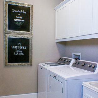 Esempio di una piccola sala lavanderia minimal con lavello a vasca singola, ante in stile shaker, ante bianche, top in superficie solida, pareti grigie, pavimento in gres porcellanato e lavatrice e asciugatrice affiancate