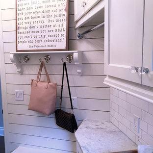 Cette photo montre une buanderie chic avec un évier encastré, un placard à porte shaker, des portes de placard blanches, un plan de travail en quartz, un mur blanc, un sol en carrelage de porcelaine et des machines côte à côte.