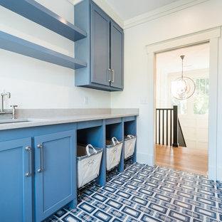 Idee per una grande sala lavanderia minimalista con lavello sottopiano, ante in stile shaker, ante blu, top in quarzo composito, pareti bianche, lavatrice e asciugatrice affiancate e pavimento multicolore