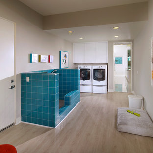 Inspiration for a midcentury utility room in Los Angeles with flat-panel cabinets, white cabinets, grey walls, light hardwood flooring and a side by side washer and dryer.