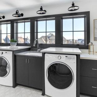 Exempel på en klassisk vita linjär vitt tvättstuga, med en undermonterad diskho, släta luckor, svarta skåp, vita väggar, en tvättmaskin och torktumlare bredvid varandra och grått golv