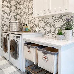 Maritim inredning av en linjär tvättstuga enbart för tvätt, med vita skåp, flerfärgade väggar, en tvättmaskin och torktumlare bredvid varandra och flerfärgat golv