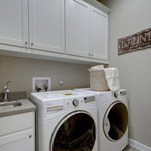 Inspiration for a transitional single-wall dedicated laundry room remodel in Jacksonville with an undermount sink, shaker cabinets, gray cabinets, gray walls and gray countertops
