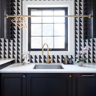 Inredning av en klassisk stor vita linjär vitt tvättstuga enbart för tvätt, med en undermonterad diskho, släta luckor, svarta skåp, bänkskiva i kvarts, svart stänkskydd, vita väggar, en tvättmaskin och torktumlare bredvid varandra och grått golv