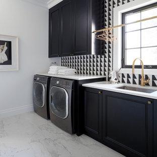 Inspiration för en stor vita linjär vitt tvättstuga enbart för tvätt, med en undermonterad diskho, släta luckor, svarta skåp, bänkskiva i kvarts, svart stänkskydd, vita väggar, en tvättmaskin och torktumlare bredvid varandra och grått golv