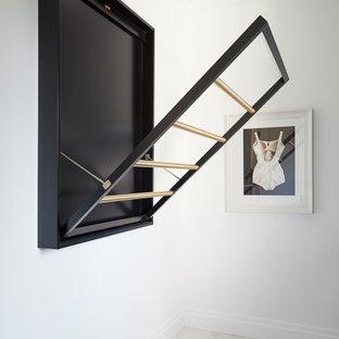 Idéer för en stor vita linjär tvättstuga enbart för tvätt, med en undermonterad diskho, släta luckor, svarta skåp, bänkskiva i kvarts, svart stänkskydd, vita väggar, en tvättmaskin och torktumlare bredvid varandra och grått golv