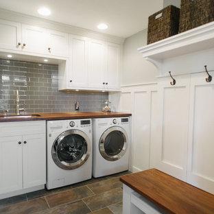 Foto på ett mellanstort amerikanskt l-format grovkök, med en undermonterad diskho, vita skåp, träbänkskiva, grå väggar, klinkergolv i porslin, en tvättmaskin och torktumlare bredvid varandra och skåp i shakerstil