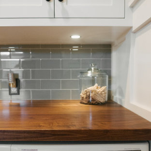 Idéer för en amerikansk l-formad tvättstuga, med en undermonterad diskho, skåp i shakerstil, vita skåp, träbänkskiva, grå väggar, klinkergolv i porslin och en tvättmaskin och torktumlare bredvid varandra