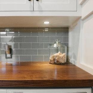 Foto di una lavanderia american style con lavello sottopiano, ante in stile shaker, ante bianche, top in legno, pareti grigie, pavimento in gres porcellanato e lavatrice e asciugatrice affiancate