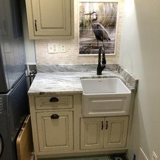 Maritim inredning av en liten bruna linjär brunt tvättstuga enbart för tvätt, med en rustik diskho, luckor med profilerade fronter, skåp i slitet trä, granitbänkskiva, gröna väggar, klinkergolv i keramik, en tvättpelare och brunt golv