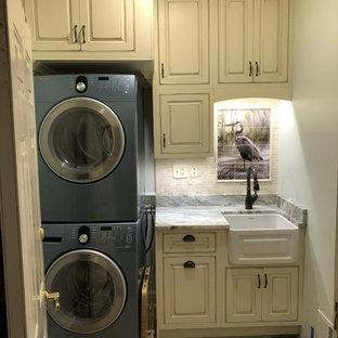 Immagine di una piccola sala lavanderia costiera con lavello stile country, ante a filo, ante con finitura invecchiata, top in granito, pareti verdi, pavimento con piastrelle in ceramica, lavatrice e asciugatrice a colonna, pavimento marrone e top marrone