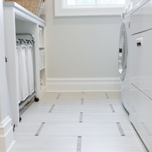 Inredning av en klassisk mellanstor parallell tvättstuga enbart för tvätt, med grå väggar, klinkergolv i porslin, en tvättmaskin och torktumlare bredvid varandra och vitt golv