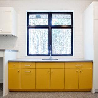 Inredning av en modern stor l-formad tvättstuga enbart för tvätt, med en undermonterad diskho, släta luckor, gula skåp, bänkskiva i kvarts, vita väggar, klinkergolv i porslin och en tvättmaskin och torktumlare bredvid varandra