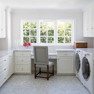 Photo of a mid-sized traditional u-shaped utility room in Orange County with raised-panel cabinets, white cabinets, a side-by-side washer and dryer, marble benchtops, white walls, porcelain floors, grey floor and grey benchtop.