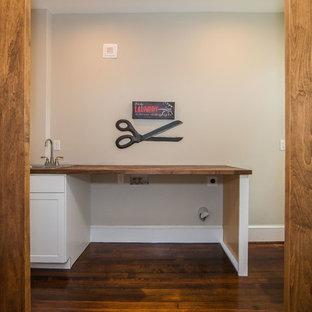 Immagine di una sala lavanderia tradizionale di medie dimensioni con lavello da incasso, ante in stile shaker, ante bianche, top in legno, pareti grigie, parquet scuro e pavimento marrone