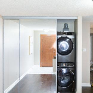 Immagine di un piccolo ripostiglio-lavanderia contemporaneo con ante di vetro, pareti beige, parquet scuro, lavatrice e asciugatrice a colonna, pavimento marrone, soffitto in perlinato e pareti in perlinato