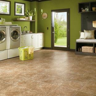 Immagine di un'ampia sala lavanderia con lavello da incasso, ante con riquadro incassato, ante bianche, pareti verdi, pavimento in vinile e lavatrice e asciugatrice affiancate