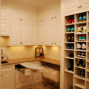 Large classic u-shaped utility room in Cleveland with a submerged sink, white cabinets, engineered stone countertops, yellow walls, porcelain flooring, a side by side washer and dryer and beaded cabinets.