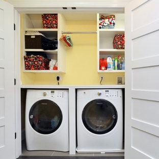 Cette image montre une petite buanderie linéaire minimaliste avec un placard, un placard sans porte, un mur jaune, un sol en bois clair, des machines côte à côte et des portes de placard blanches.