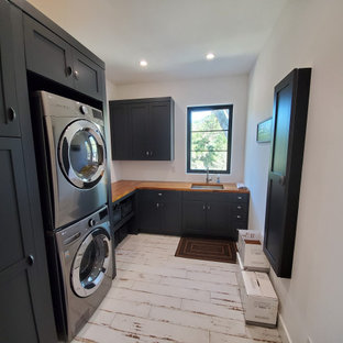 This is an example of a mid-sized country l-shaped utility room in San Francisco with an undermount sink, shaker cabinets, blue cabinets, wood benchtops, white walls, porcelain floors, a stacked washer and dryer, white floor and orange benchtop.