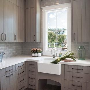 Inspiration för mellanstora klassiska l-formade vitt tvättstugor enbart för tvätt och med garderob, med en rustik diskho, grå skåp, mellanmörkt trägolv, släta luckor, bänkskiva i kvarts, grått stänkskydd, stänkskydd i tunnelbanekakel, grå väggar och brunt golv