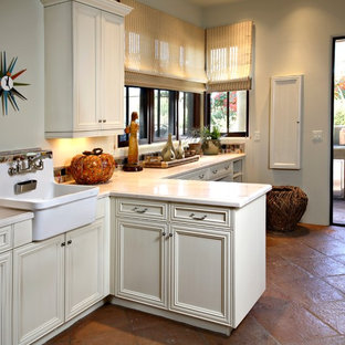 Example of a large tuscan single-wall terra-cotta tile and red floor dedicated laundry room design in Phoenix with beige cabinets, gray walls, a farmhouse sink, recessed-panel cabinets, quartz countertops and a side-by-side washer/dryer