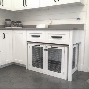 Foto på ett mellanstort lantligt grå grovkök, med en undermonterad diskho, luckor med profilerade fronter, vita skåp, bänkskiva i kvarts, vita väggar, klinkergolv i keramik, en tvättpelare och grått golv