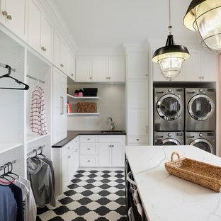 На фото: п-образная универсальная комната в классическом стиле с врезной раковиной, фасадами в стиле шейкер, белыми фасадами, розовыми стенами, с сушильной машиной на стиральной машине и белой столешницей