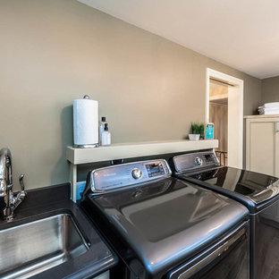 Foto på ett mycket stort vintage parallellt grovkök, med en undermonterad diskho, beige skåp, bänkskiva i kvarts, grå väggar, klinkergolv i porslin, en tvättmaskin och torktumlare bredvid varandra och luckor med infälld panel