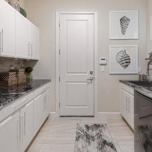Idéer för att renovera ett vintage svart parallellt svart grovkök, med en nedsänkt diskho, släta luckor, vita skåp, granitbänkskiva, beige stänkskydd, stänkskydd i stenkakel, beige väggar, klinkergolv i porslin, en tvättmaskin och torktumlare bredvid varandra och beiget golv