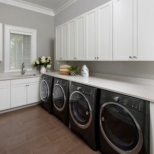 Design ideas for a large modern l-shaped separated utility room in DC Metro with a submerged sink, flat-panel cabinets, white cabinets, engineered stone countertops, grey walls, porcelain flooring, a side by side washer and dryer and brown floors.