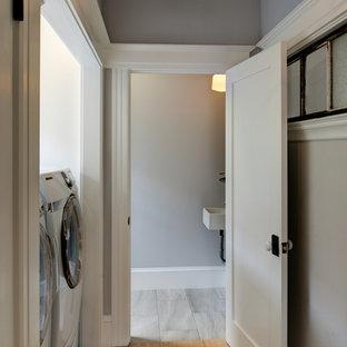 Ejemplo de armario lavadero lineal, ecléctico, pequeño, con paredes grises, suelo de madera clara, lavadora y secadora juntas y suelo marrón