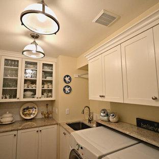 Klassisk inredning av ett litet parallellt grovkök, med en undermonterad diskho, luckor med infälld panel, granitbänkskiva, beige väggar, ljust trägolv och en tvättmaskin och torktumlare bredvid varandra