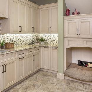 Inspiration för en mellanstor lantlig l-formad tvättstuga enbart för tvätt, med en undermonterad diskho, luckor med infälld panel, beige skåp, granitbänkskiva, travertin golv, en tvättmaskin och torktumlare bredvid varandra, beiget golv och grå väggar