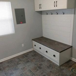 Réalisation d'une buanderie design avec un placard avec porte à panneau encastré, des portes de placard blanches, un plan de travail en stratifié, une crédence blanche, une crédence en lambris de bois, un mur gris, un sol en linoléum, un sol marron et un plan de travail marron.