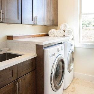 Idee per una sala lavanderia minimal di medie dimensioni con lavello sottopiano, ante in stile shaker, top in quarzo composito, pareti bianche, pavimento in travertino, lavatrice e asciugatrice affiancate, pavimento beige e ante in legno bruno
