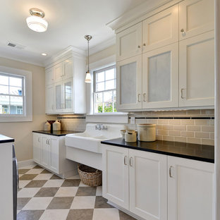 Large classic galley utility room in Charleston with an utility sink, recessed-panel cabinets, white cabinets, composite countertops, beige walls, a side by side washer and dryer, multi-coloured floors and black worktops.