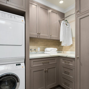 Example of a mid-sized classic l-shaped gray floor and porcelain tile dedicated laundry room design in Los Angeles with recessed-panel cabinets, gray cabinets, marble countertops, beige walls and a stacked washer/dryer