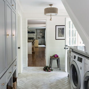 На фото: параллельная универсальная комната в стиле современная классика с фасадами в стиле шейкер, серыми фасадами, белыми стенами, со стиральной и сушильной машиной рядом, серым полом, серой столешницей и стенами из вагонки с