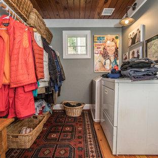 Rustik inredning av ett mellanstort parallellt grovkök, med grå väggar, mellanmörkt trägolv, en tvättmaskin och torktumlare bredvid varandra och brunt golv
