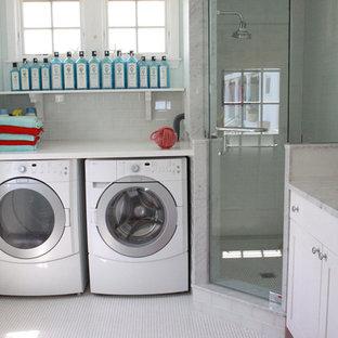 Maritim inredning av ett stort vit l-format vitt grovkök, med en undermonterad diskho, skåp i shakerstil, vita skåp, marmorbänkskiva, blå väggar, klinkergolv i keramik, en tvättmaskin och torktumlare bredvid varandra och gult golv