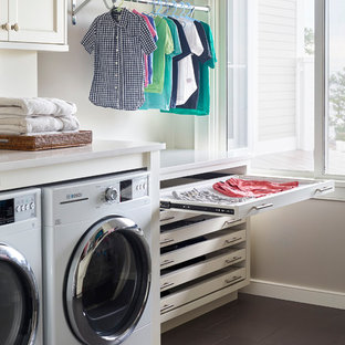 Inredning av en maritim vita vitt tvättstuga enbart för tvätt, med vita skåp, grå väggar, en tvättmaskin och torktumlare bredvid varandra, grått golv och skåp i shakerstil