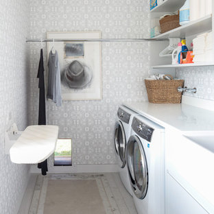 Exempel på en mellanstor modern linjär tvättstuga enbart för tvätt, med vita väggar och en tvättmaskin och torktumlare bredvid varandra