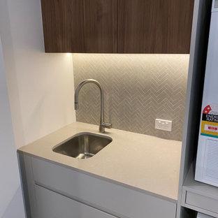 Inspiration för små moderna u-formade grått tvättstugor, med en undermonterad diskho, luckor med profilerade fronter, grå skåp, bänkskiva i kvarts, grått stänkskydd, stänkskydd i keramik, laminatgolv och brunt golv