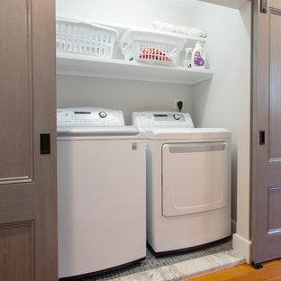 Exemple d'une petit buanderie linéaire tendance avec un placard, un mur blanc, un sol en carrelage de céramique et des machines côte à côte.